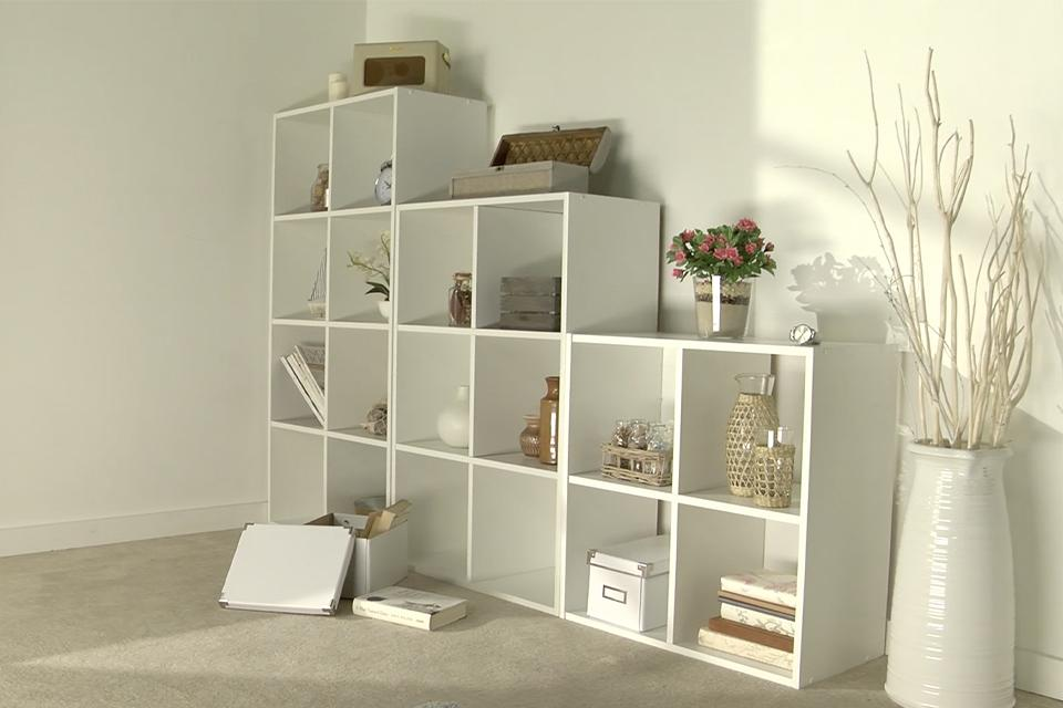 Image of white a cube storage unit against a wall.
