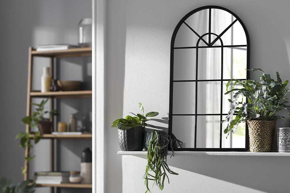 A black window-style mirror on a floating shelf with plants above a sofa.