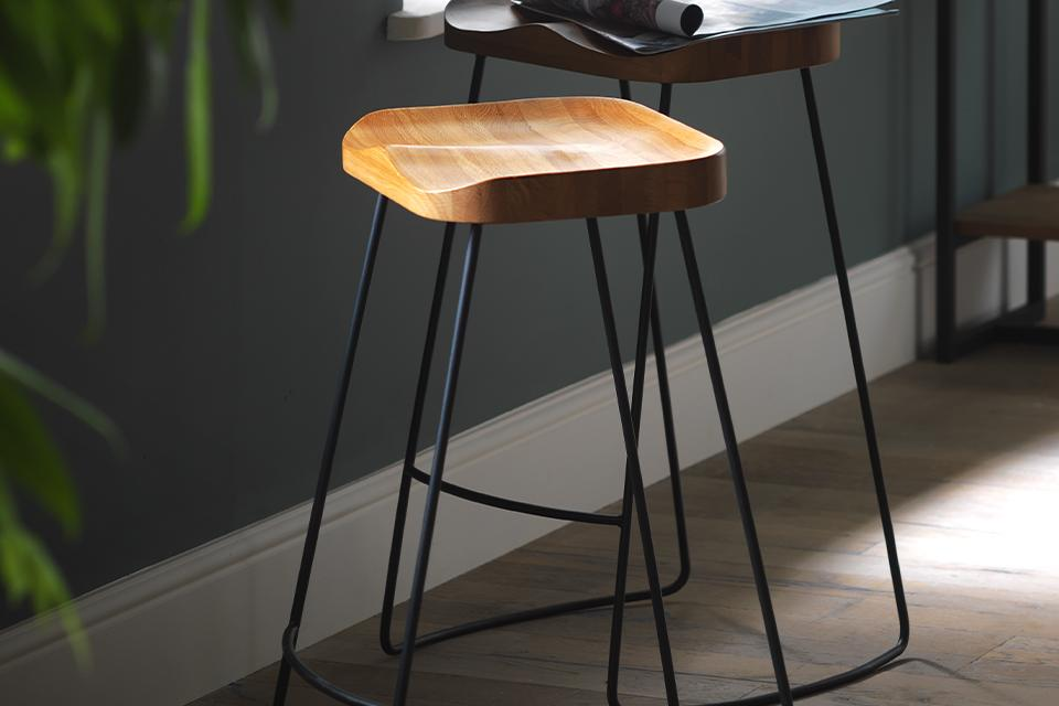 Image of a pair of wooden dining stools against the wall.