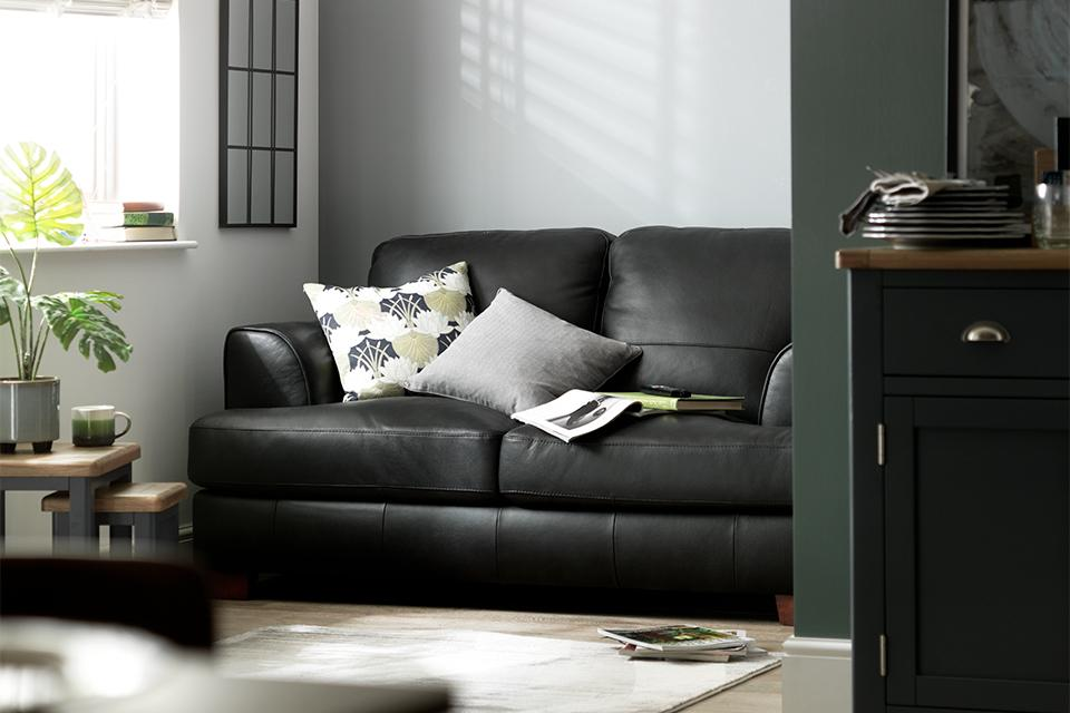 Image of black sofa with cushions in living room.