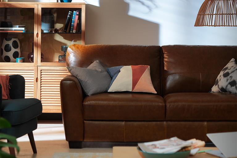 Image of a leather sofa with cushions in a living room.