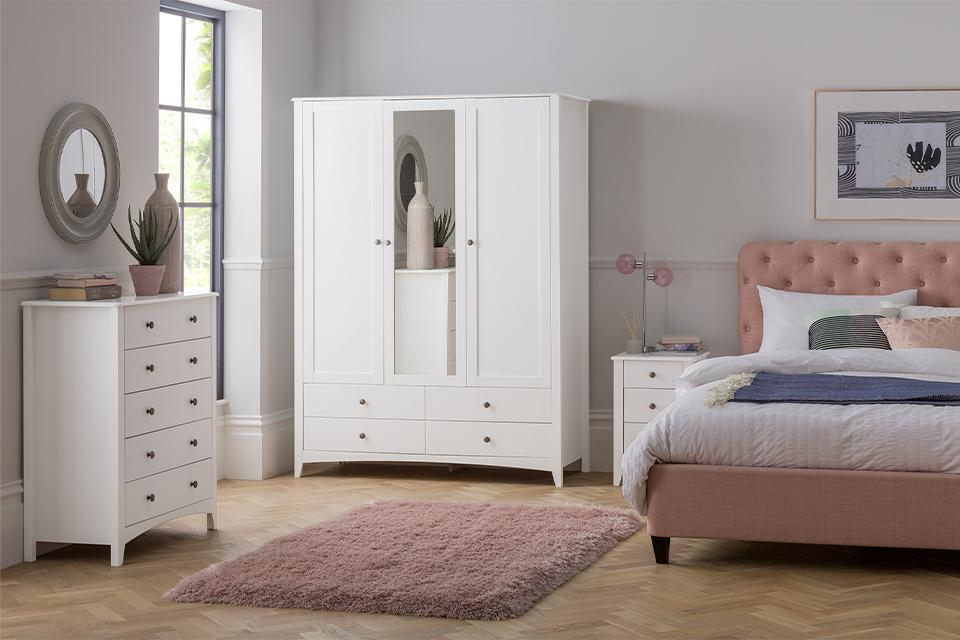 Bedroom with white bedroom furniture set and pink bed.