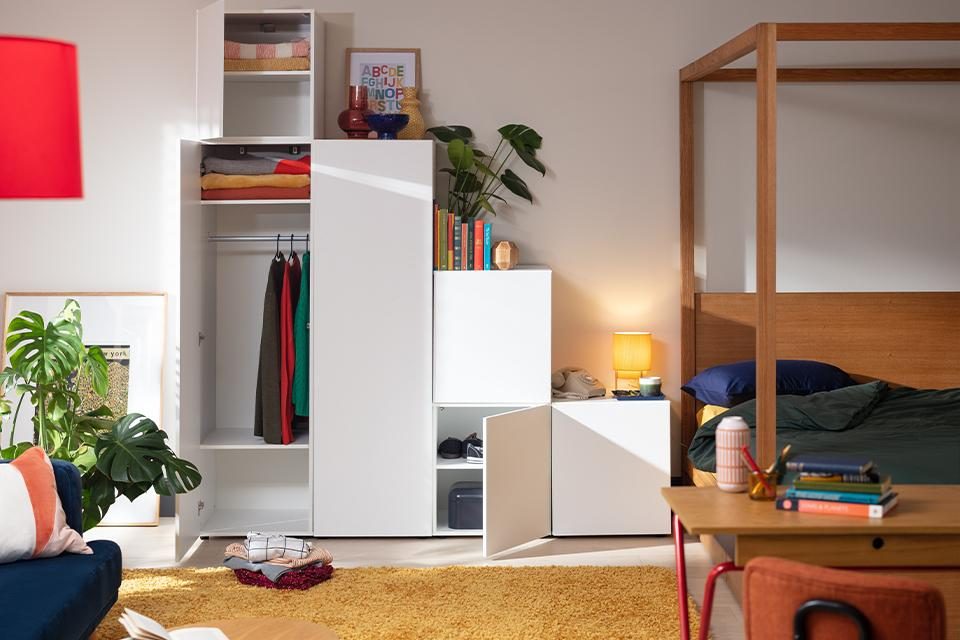 A white wardrobe and matching cube storage beside a wooden four poster bed.