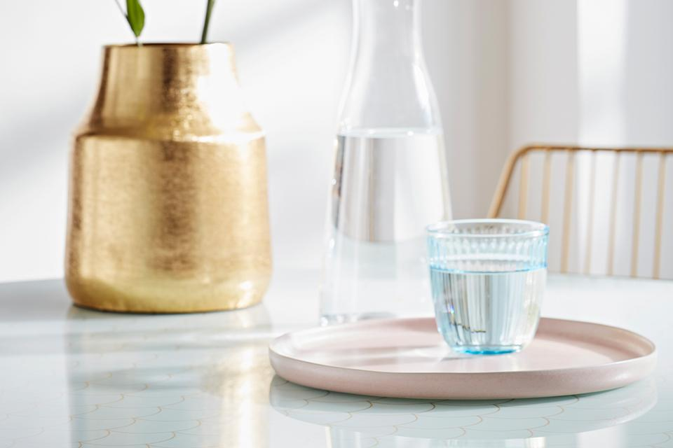A textured glass tumbler on a pale pink serving tray with a brushed gold plant pot in the background.