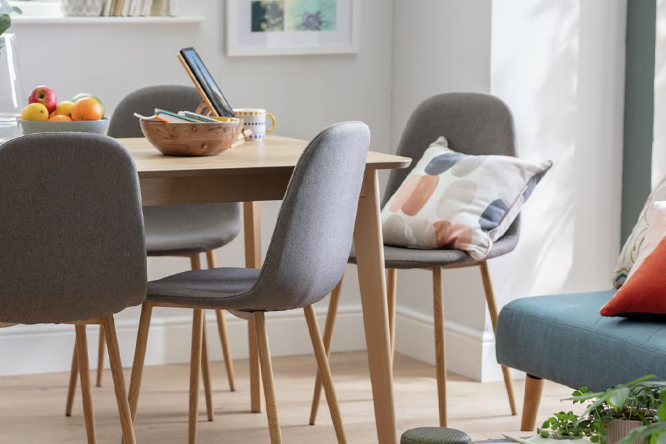 Grey upholstered dining chairs with rounded backs twinned with a Scandi-style dining table.
