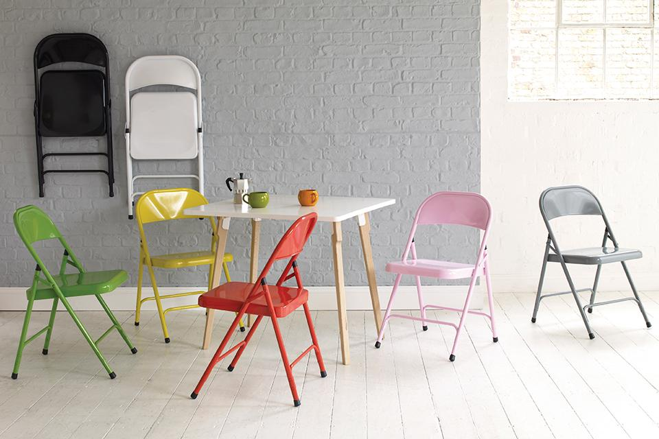 Brightly coloured folding chairs around a square white dining table.