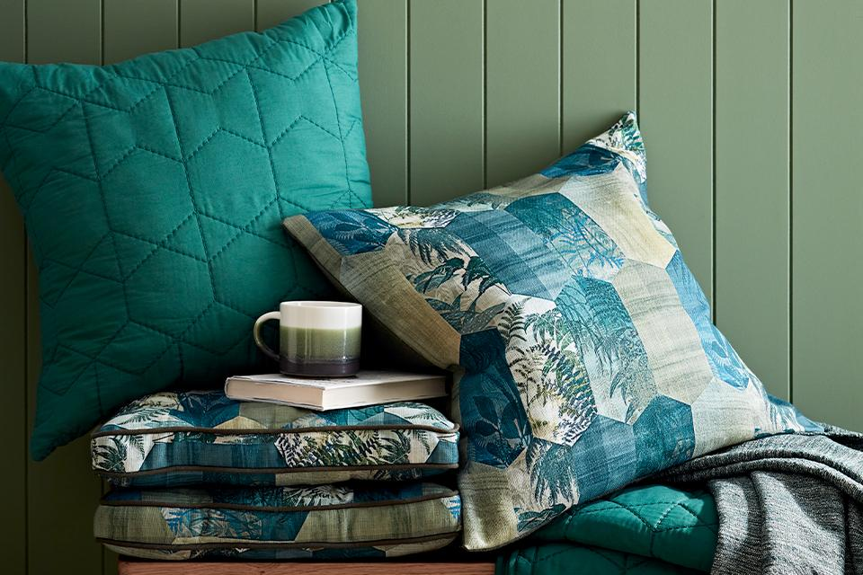 A stack of plain and patchwork teal cushions on a wooden bench.
