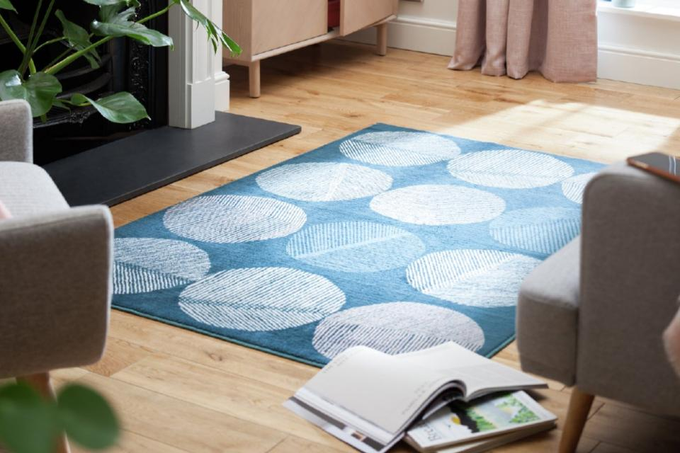A blue rug with large cream circles on a wooden floor.
