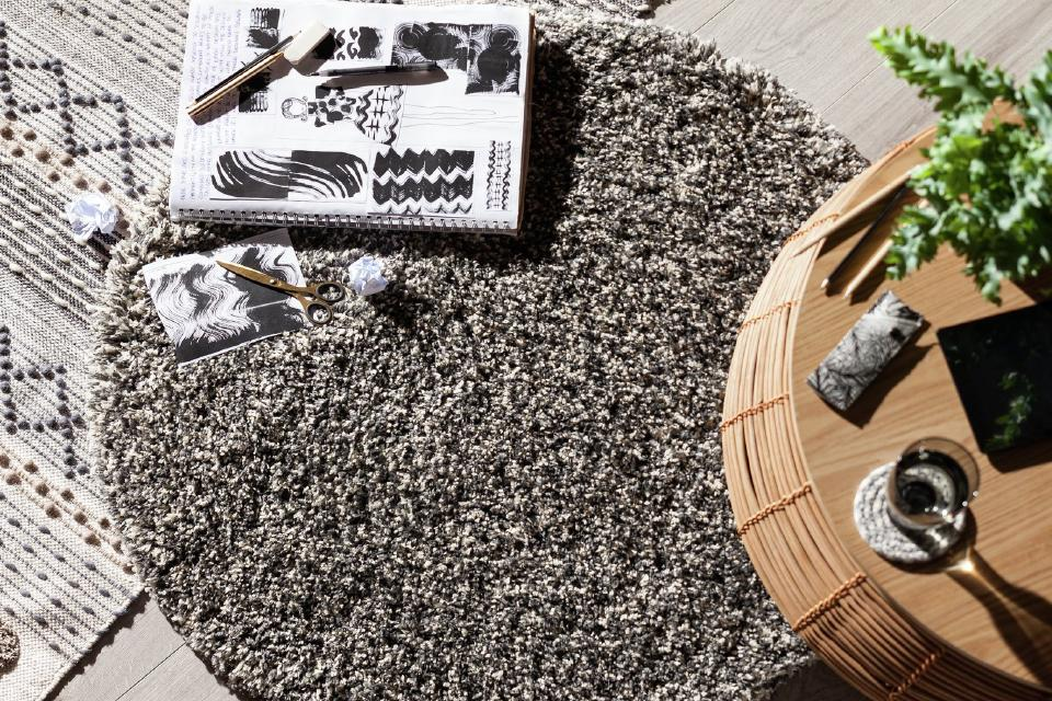 A thickly woven speckled rug beside a round bamboo side table.