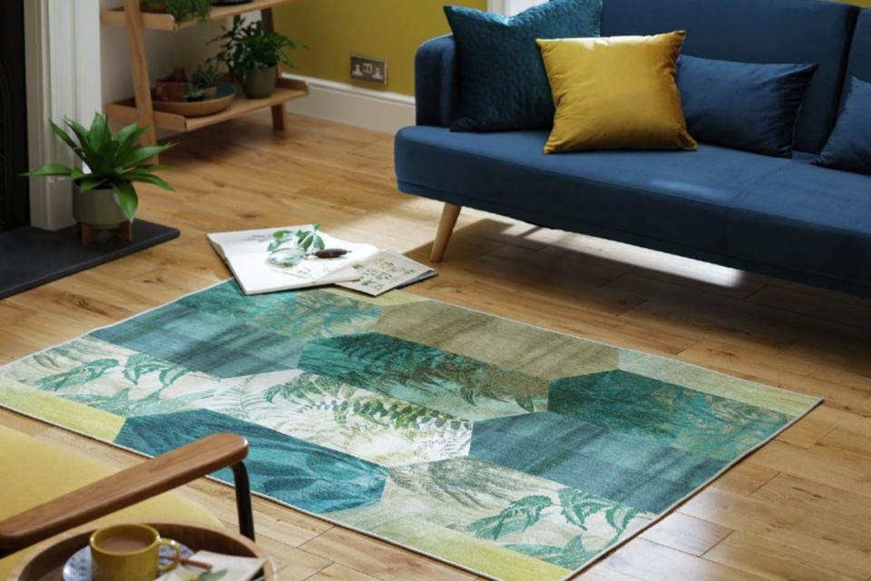 A blue-green patchwork rug on a wooden floor beside a navy blue sofa.
