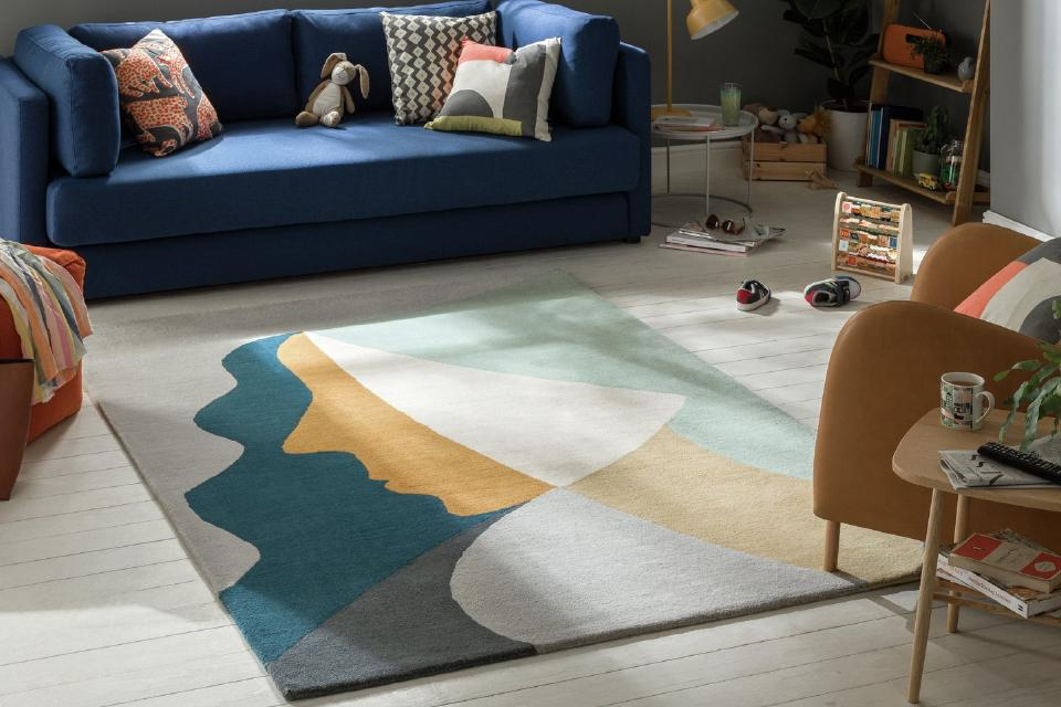 An abstract pastel coloured rug on a white wooden floor beside a navy blue sofa.