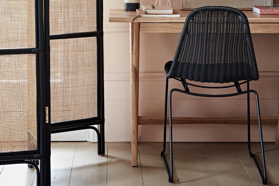 Home office with oak desk, black rattan chair and rattan screen room divider.
