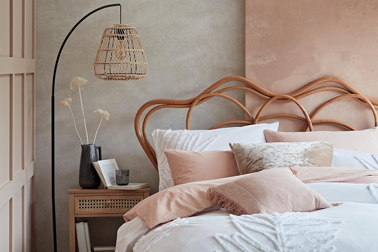 A soft pastel bedroom with rattan accents and textured white bed linen with pink throw cushions.