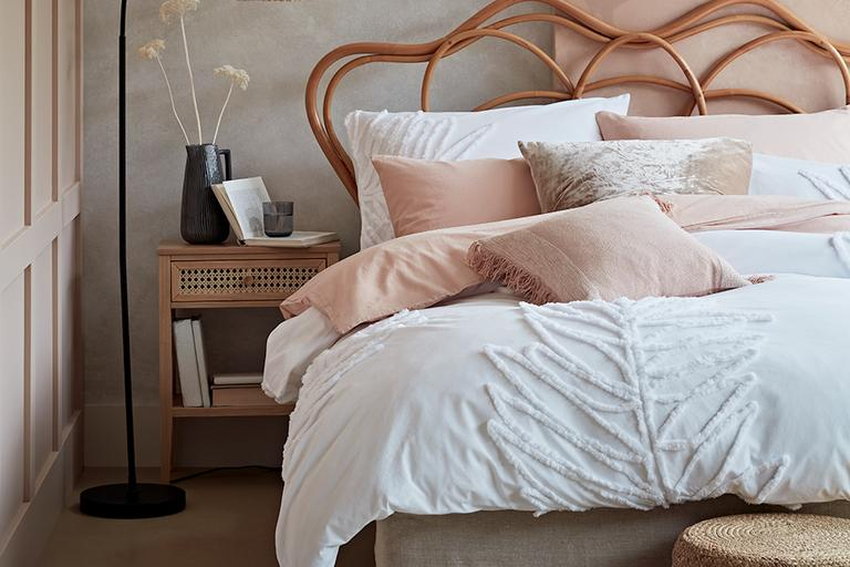 Rattan bed with white and pink bedding.
