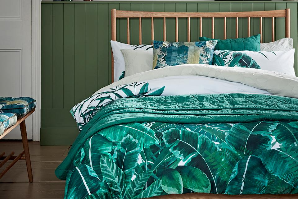 Bold leaf print bedding on a wooden bed in a green bedroom.