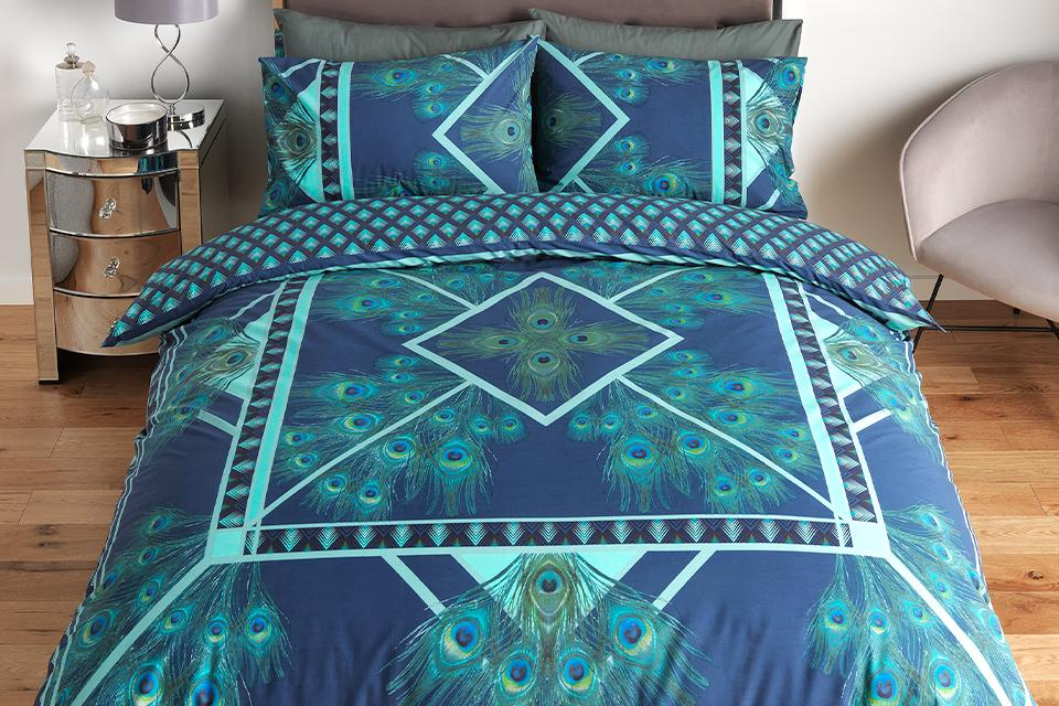 Image of a double bed with blue and turquoise, peacock design bedding.