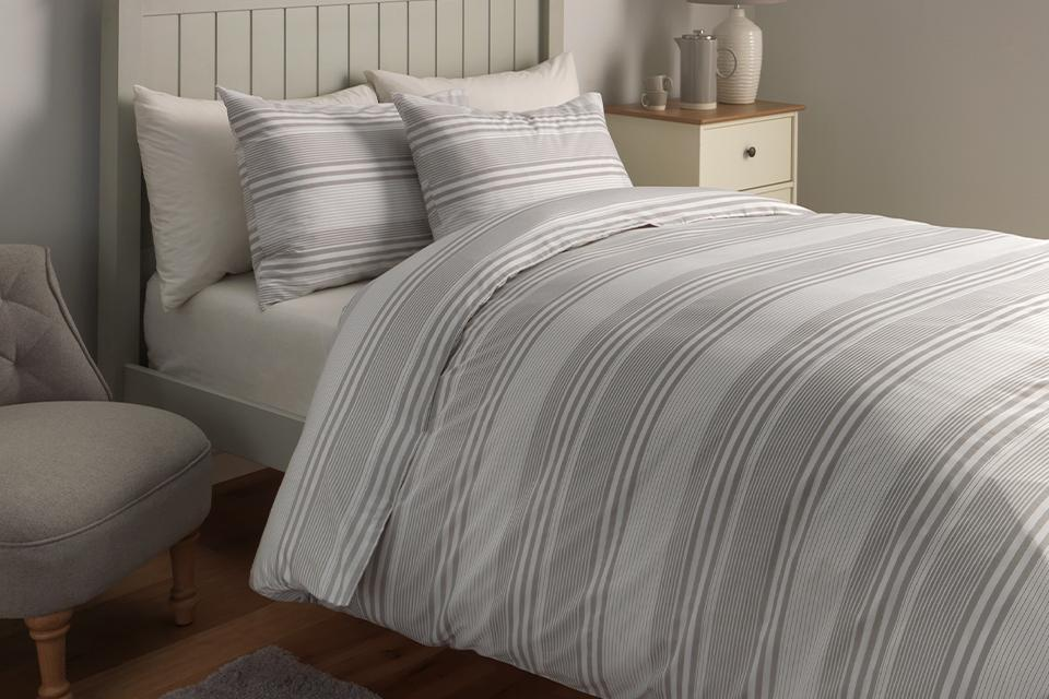 Image of a single bed with white and grey striped bedding.