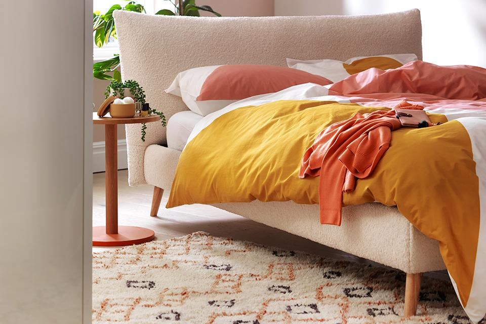 An upholstered bed with brightly coloured linen in a pale pink room.