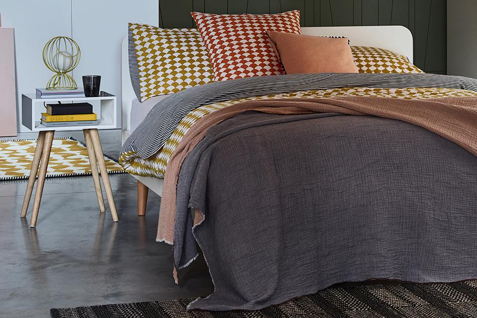 Image of a super king size bed with grey, orange and yellow bedding.