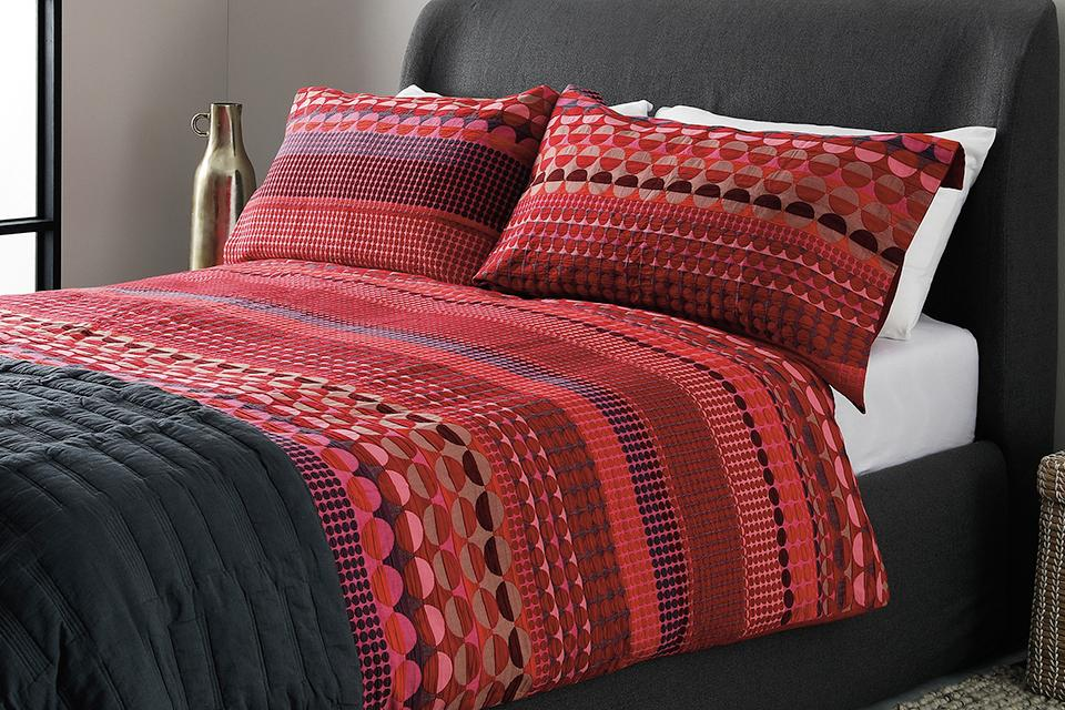 Image of a king size bed with a black, red and purple patterned duvet.