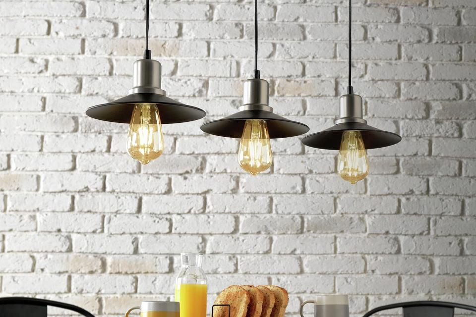 Image of a trio of black industrial style pendants over a dining table.