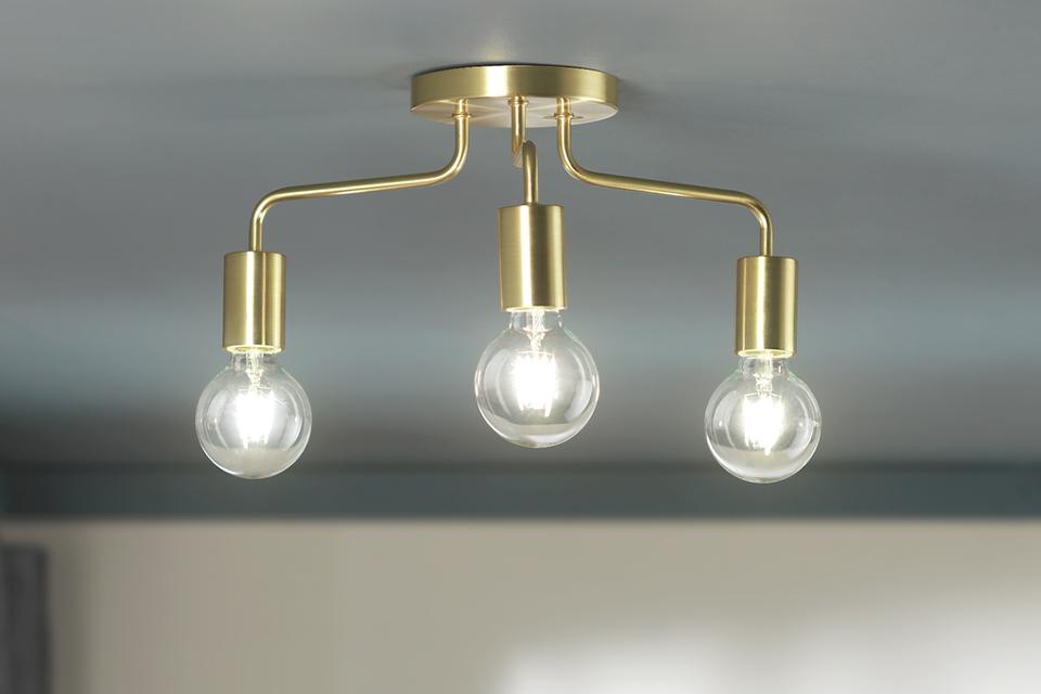 Image of a gold light bar with 3 exposed bulbs.