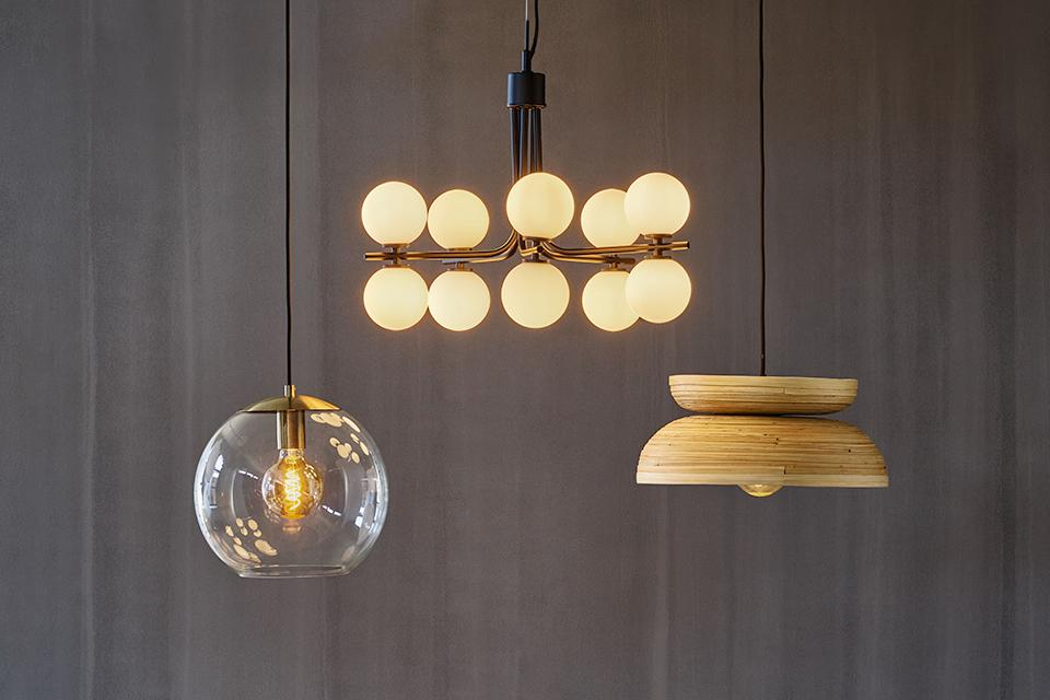 Image of three pendant lights in various styles hanging over a black dining table.
