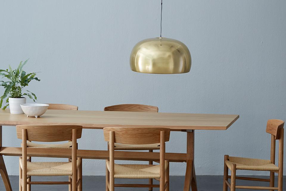 Image of a gold metal domed pendant shade hanging over a dining table.