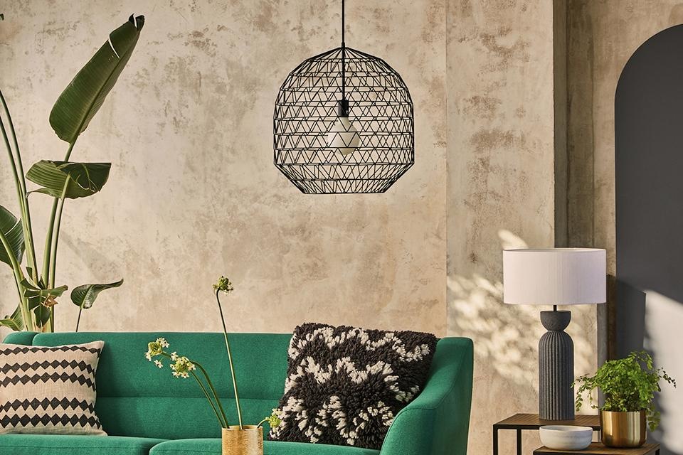 Image of a green sofa in a living room and a pendant with a black caged shade next to it.