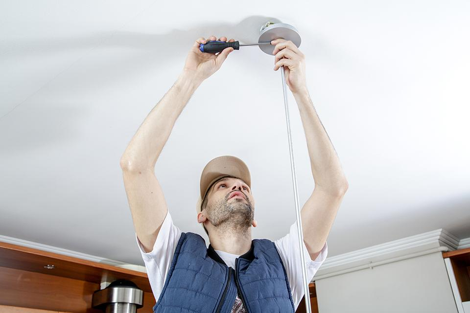 Image of a man screwing a pendant light to the ceiling.