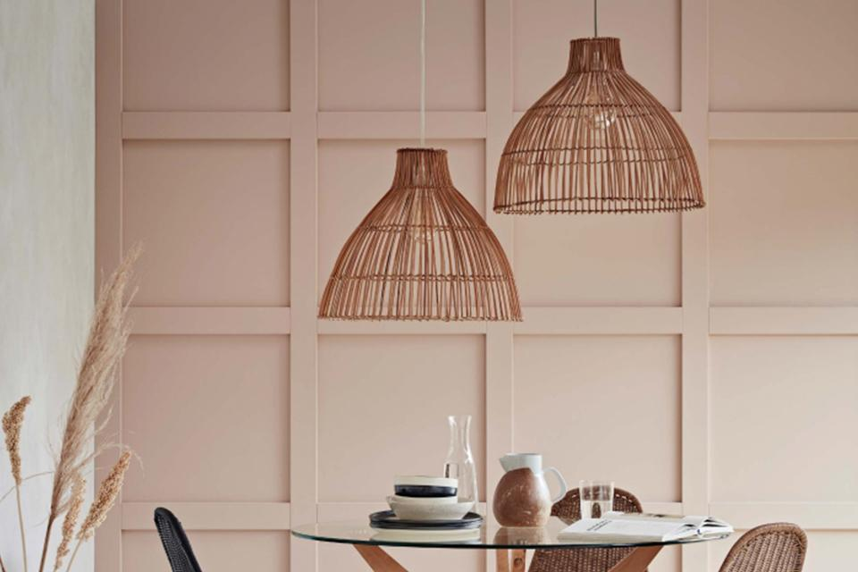 Image of a small dining table with two pendants hanging over it with rattan shades.