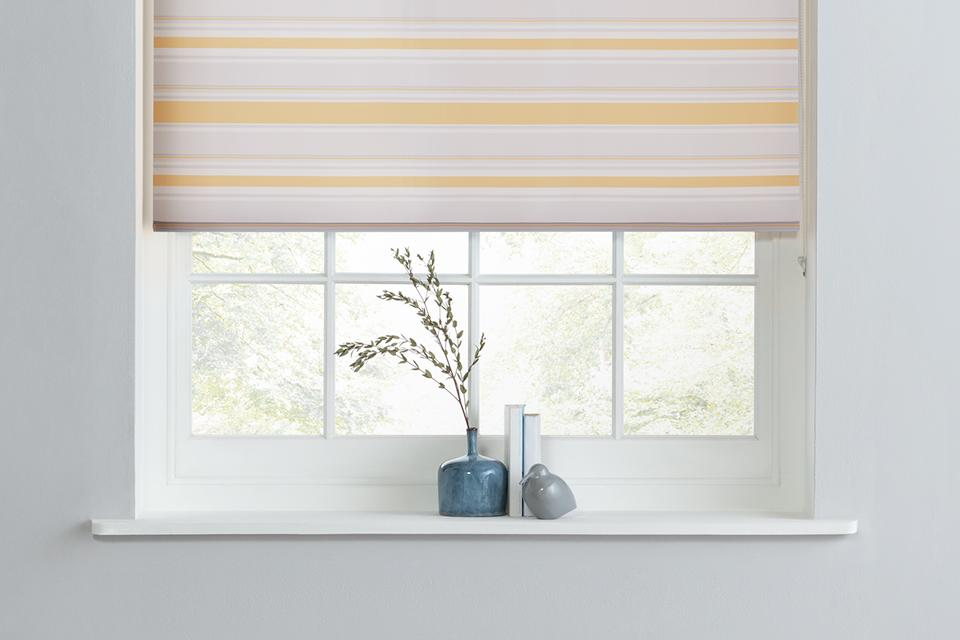 A horizontally striped rolled blind in a white window space.