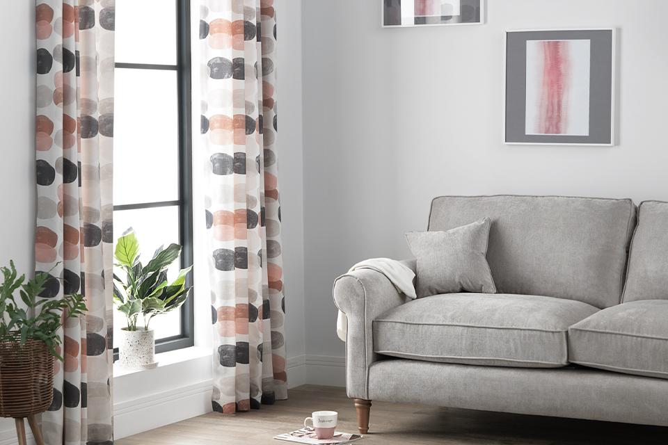 Pink, grey and white spotted curtains in a living room with matching accents.