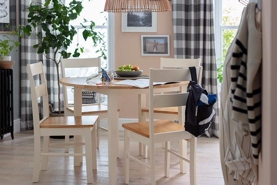 A white and natural wood round dining set in the middle of a dining space.