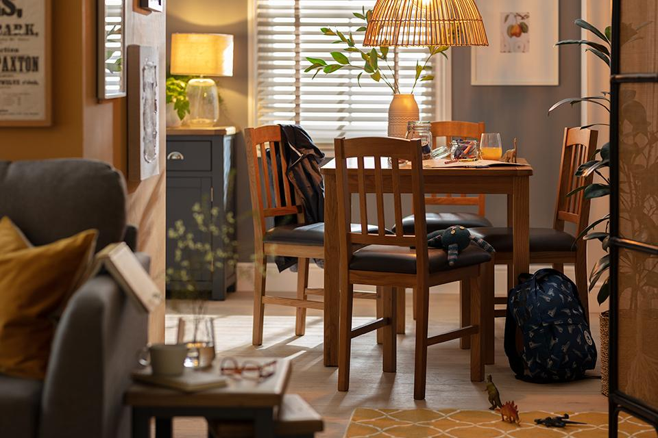 A square wooden dining set in a cosy living space.