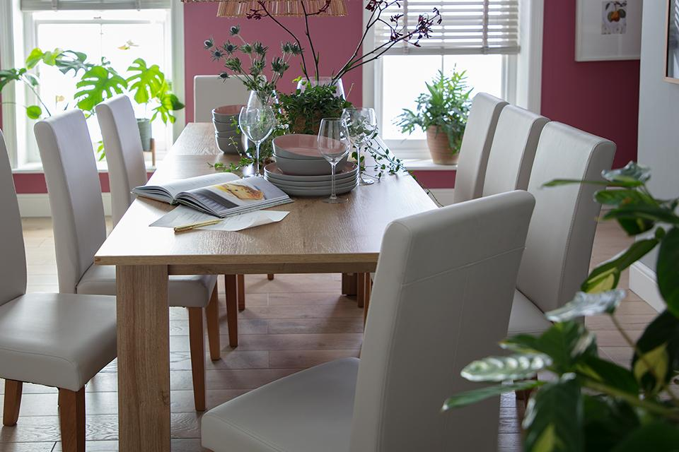 A long rectangular wooden dining table with matching upholstered chairs.