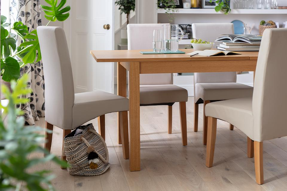 A rectangular wooden dining table with matching upholstered chairs.