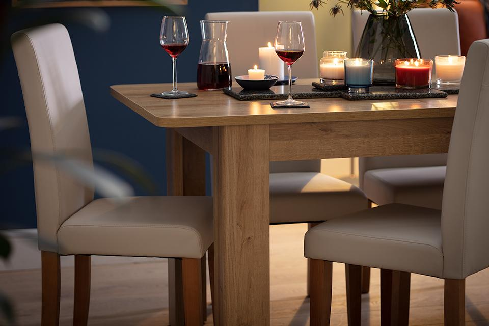 A natural wood rectangular dining set laid out for a meal with wine and candles.