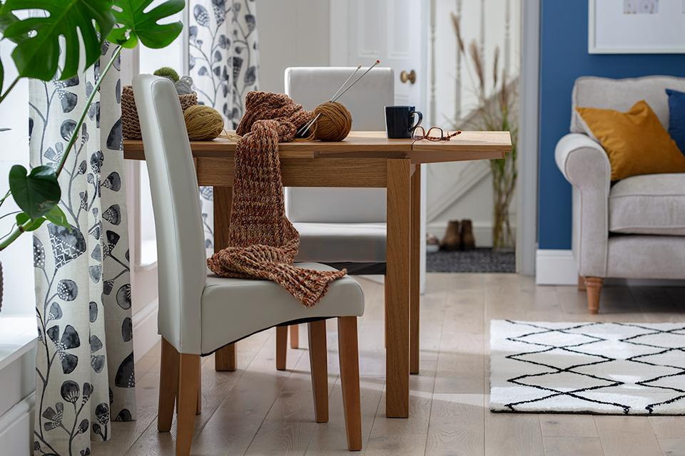 A wooden drop leaf dining table with two upholstered chairs in an open plan living room.