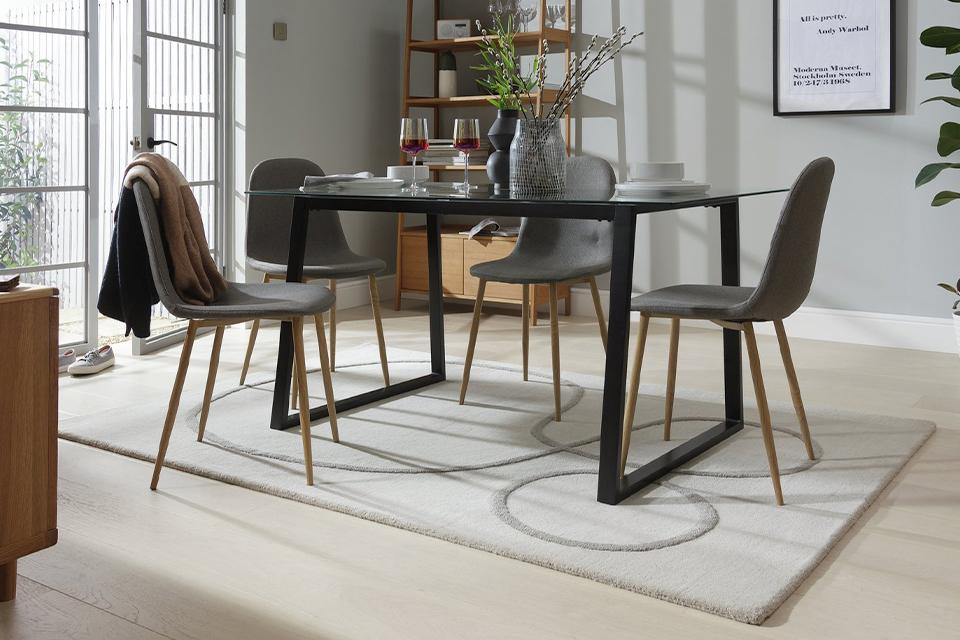 A glass-topped dining table with black legs and grey upholstered chairs.