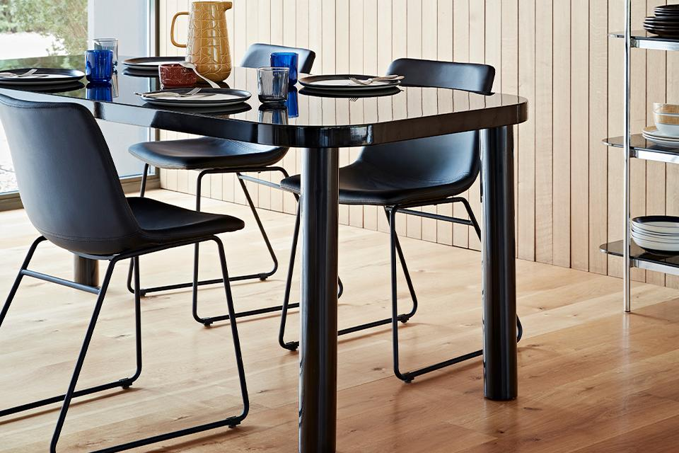 A black dining table with a glass top and rounded corners with black mid-century style chairs.