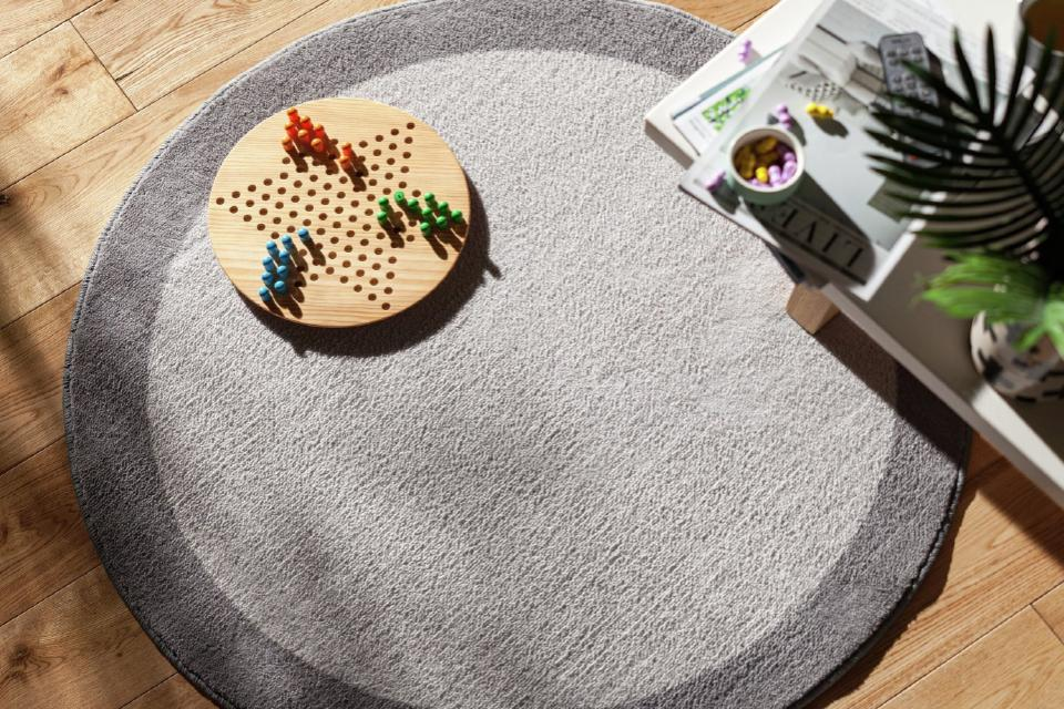 A round, two-tone grey rug with a game laid out on top of it.