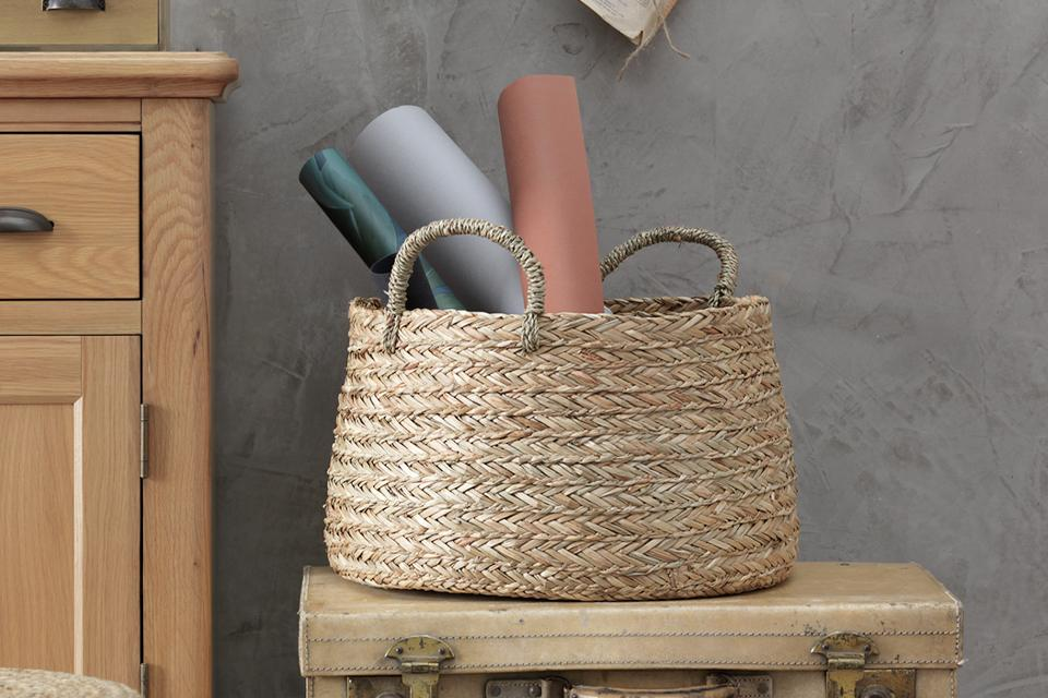 A rattan basket beside an oak cabinet.