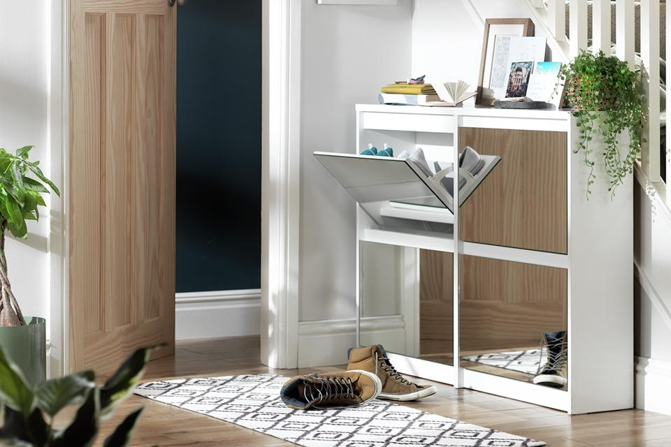 Mirrored shoe storage unit with one cabinet open. White geometric rug placed in front of the cabinet.