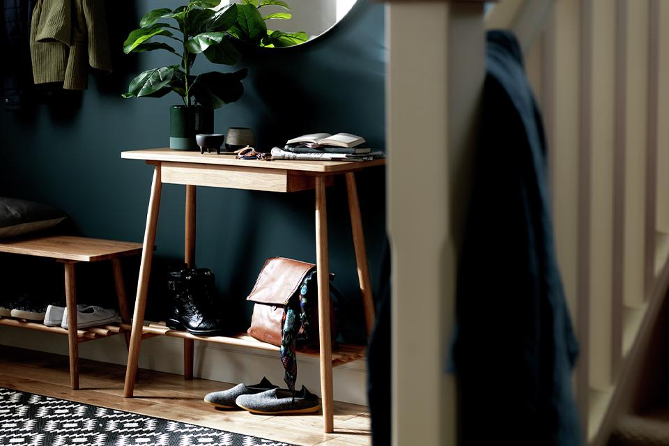 A narrow-legged oak console table in a dark green hallway.