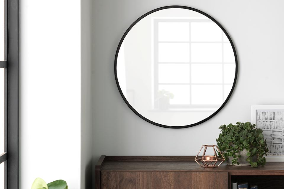 A round, black-rimmed mirror on a white wall above a walnut sideboard.
