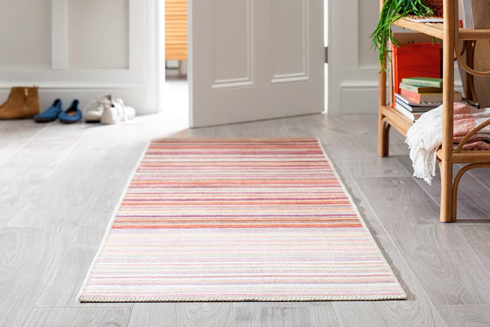 A warm-toned striped runner in a neutral hallway.