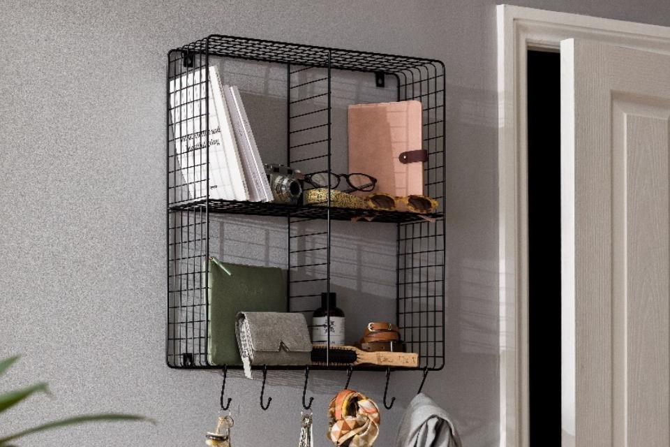 A black mesh wall organiser with hanging hooks and storage space.