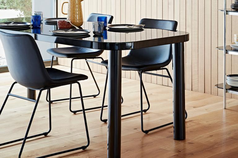 Dining room with mid-century black gloss dining table and four faux leather dining chairs.