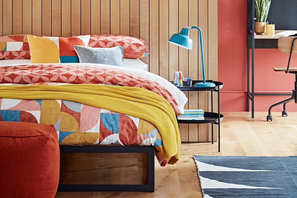 A mid-century styled bedroom with bold, bright colours and geometric shapes.
